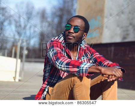 Outdoor Fashion Portrait Of Stylish Young African Man Listens To Music And Enjoys Freedom In The Cit