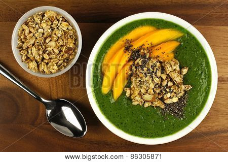 Green smoothie bowl with mangoes, granola and chia seeds