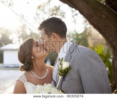 Young newly married couple kissing outdoors