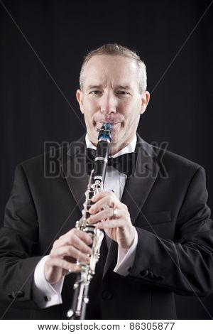 Man in tuxedo playing clarinet over black background