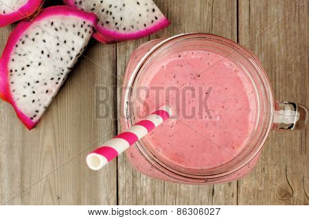 Dragon fruit smoothie with fruit slices on wood
