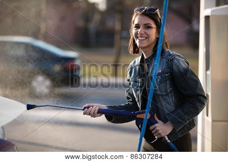 Attractive woman washing automobile at manual car washing self service,cleaning with pressured foam