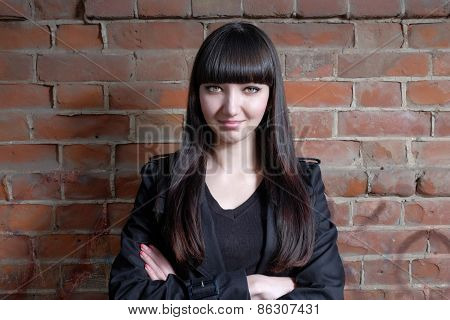Woman crossed arms standing against red brick wall. Confident pose. Looking at camera