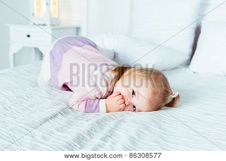 Cute Little Blonde Girl On Hands And Knees On White Bed In Bedroom