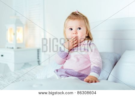 Funny Surprised Blond Little Girl Sitting On Bed In Bedroom