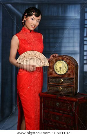 Chinese Girl in traditional red dress holding a fan in hand