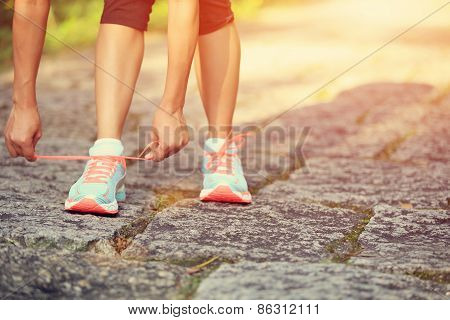 young woman runner tying shoelaces on country road