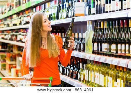 Woman buying wine in supermarket store