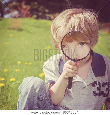 Preschool boy looking through a magnifying glass.