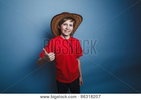 boy teenager European appearance in a red shirt brown hat showin