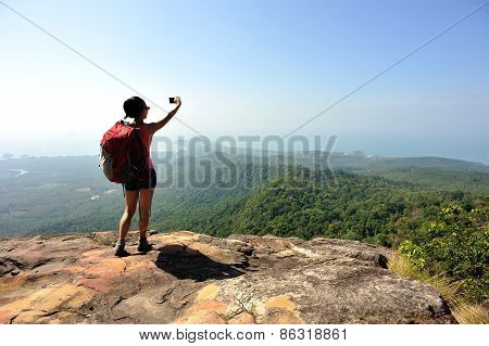 woman hiker taking photo with digital camera at mountain peak cliff