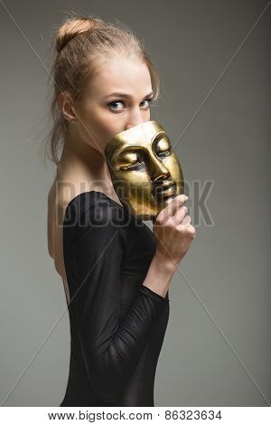 graceful ballerina with a bronze metal mask