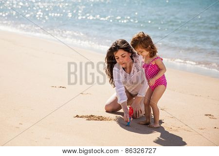 Mom And Daughter Writing In Sand