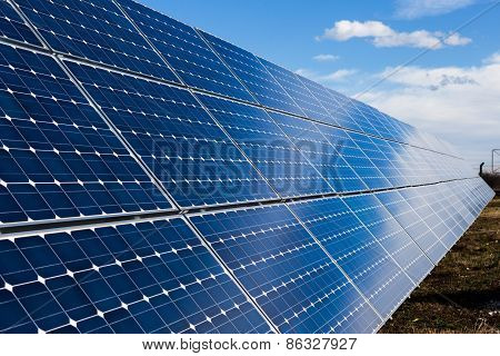 Row Of Solar Panels And Cloudy Sky