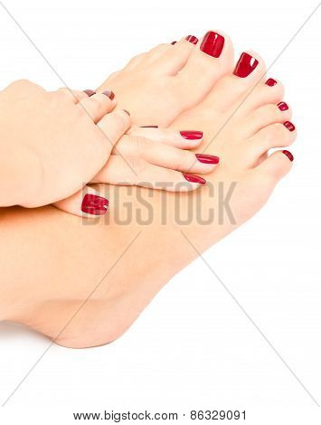 Female feet and hands with red manicure