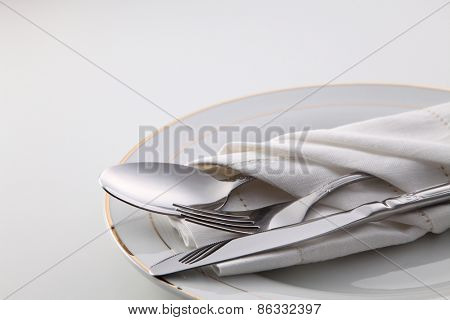 Folded napkin with fork, spoon and knife, on plate