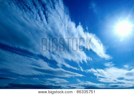 the Sun and white fluffy clouds on a blue sky