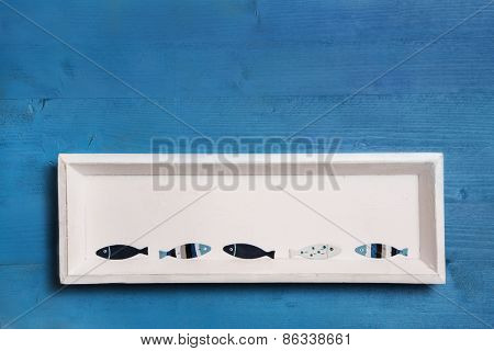 Wooden blue background with a white wooden sign and fishes.
