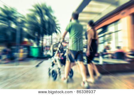 Motion Blurred Couple With Baby Stroller In The Shopping Center