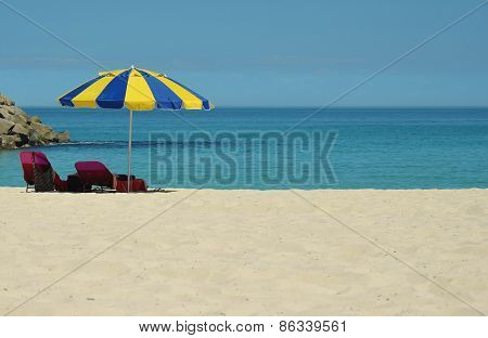 Sun lounger under an umbrella on the beach