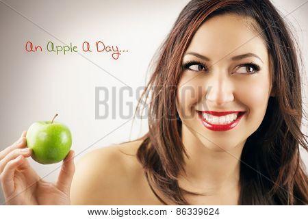 Woman holding apple smiling on brown background. Healthy eating candid woman.