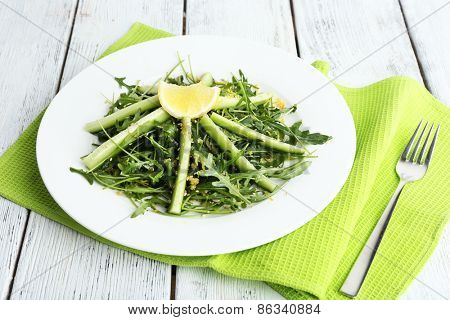 Plate of green salad with cucumber, arugula and rosemary on wooden background