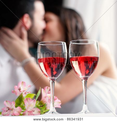 Wine Glasses With Couple Kissing In Background.