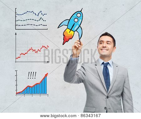 business, development, management and people concept - happy smiling businessman in suit writing or drawing something imaginary with marker over gray background