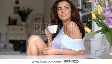 Gorgeous dark haired young woman sitting drinking coffee at a table in her living room looking at the camera with a lovely smile