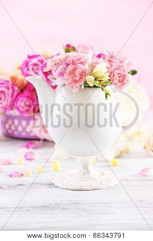 Composition with beautiful spring flowers in teapot on light pink background