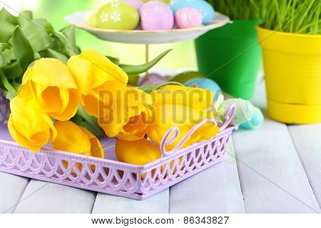 Yellow tulips and Easter eggs on table on natural background