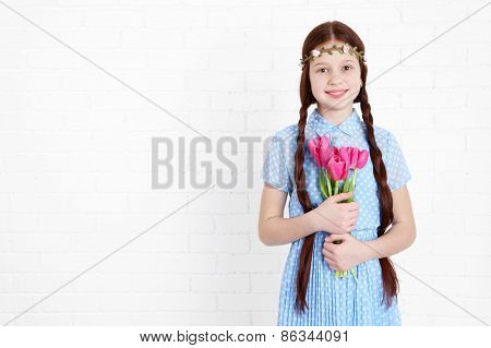 Beautiful little girl on bricks wall background