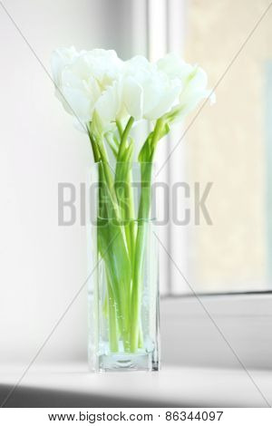 Beautiful white tulips in glass vase on windowsill background