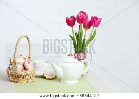 Tea set with flowers on table, on light background