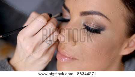 Beautician apply makeup to a glamour model darkening and enhancing the edges of her eyelids
