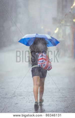 Girl walking at summer rain in the city