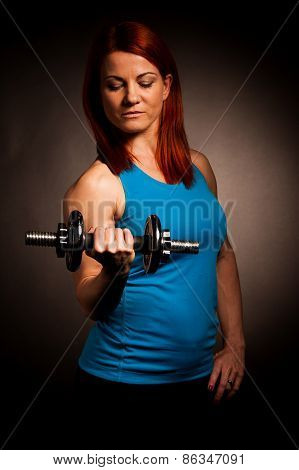 Beautiful Young Woman Working Out With Dumbels In Fitness Gym