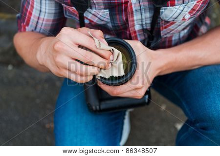 Photographer Cleaning Lens.