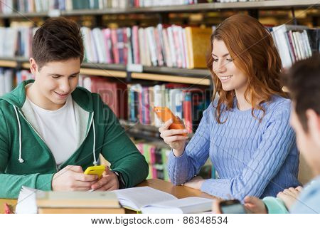 people, education, technology and school concept - group of happy students with smartphones and books texting message or networking in library