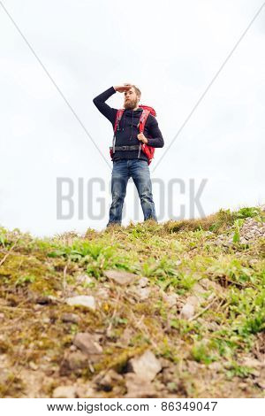 travel, tourism, hike and people concept - tourist with beard, backpack standing on edge of hill and looking far away