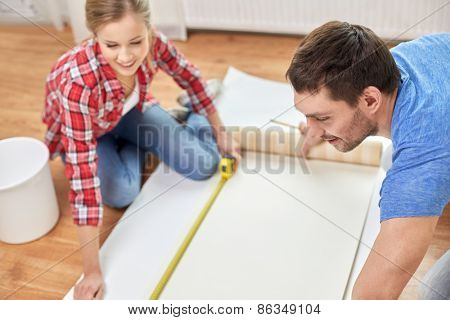 repair, building and people concept - close up of couple with ruler measuring wallpaper at home