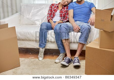 moving, home, repair and people concept - close up of couple legs relaxing and sitting on sofa in new apartment