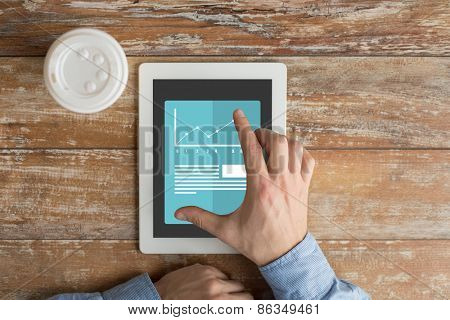 business, education, people and technology concept - close up of male hands with graph and text on tablet pc computer screen and coffee cup on table