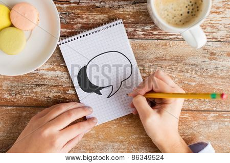 business, education and people concept - close up of female hands drawing text bubble in notebook with pencil, coffee and cookies on table