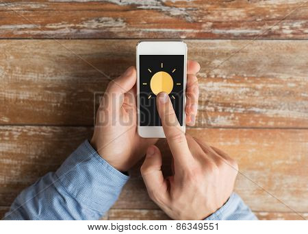 people, weather forecast and technology concept - close up of male hands with sun icon on smartphone screen