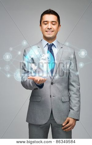 business, people, technology, connection and communication concept - happy businessman in suit showing network contacts and globe hologram over gray background