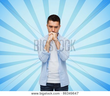 sadness, problem, sorrow and people concept - unhappy man thinking over blue burst rays background
