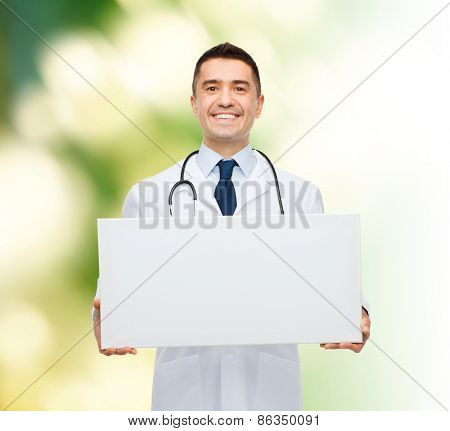 healthcare, advertisement, people and medicine concept - smiling male doctor in white coat holding white blank board over green background