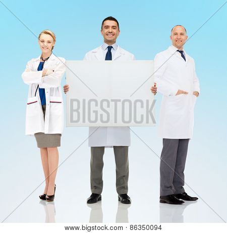 healthcare, advertisement, people and medicine concept - group of smiling doctors holding white blank board over blue background