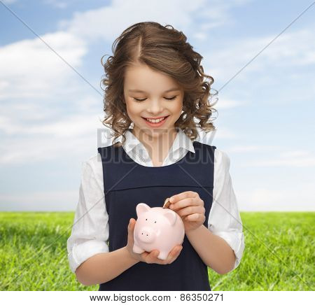 people, money, finances and savings concept - happy girl holding piggy bank and putting coin over blue sky and grass background